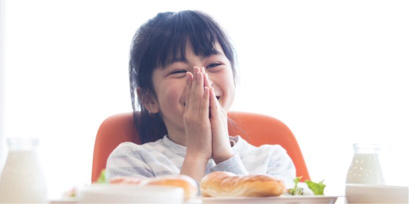 給食を食べている笑顔の女の子